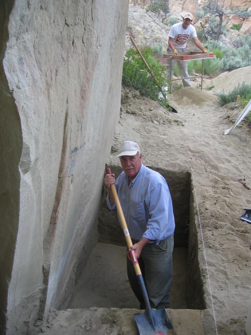 Larry Loendorf excavating in front of Main rock art panel  Valley of the Shields  Montana